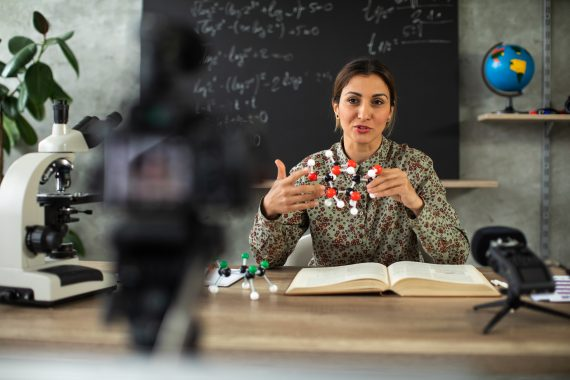 Female teacher sitting at desk in front of blackboard and recording science lesson using video camera from home during coronavirus pandemic.
